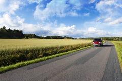 Conducción de automóviles en un camino recto estrecho Imágenes de archivo libres de regalías