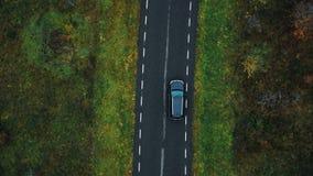 Conducción de automóviles negra de seguimiento de la cámara de opinión superior del abejón en la carretera vacía a lo largo del b almacen de metraje de vídeo