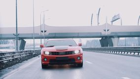 Conducción de automóviles roja del músculo hacia cámara en la carretera metrajes