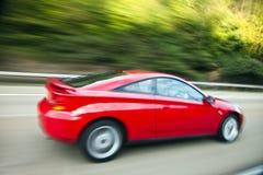Conducción de automóviles roja rápidamente en la carretera nacional Imágenes de archivo libres de regalías