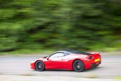 Conducción de automóviles roja rápidamente en la carretera nacional Imagen de archivo libre de regalías