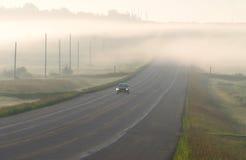 Conducción de automóviles a través de la niebla Imágenes de archivo libres de regalías