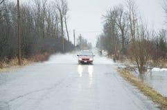 Conducción de automóviles a través del camino inundado Imágenes de archivo libres de regalías