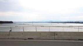Conducción de automóviles a través del puente con vistas a un río almacen de metraje de vídeo