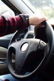 Conducción de la mano del coche en el volante Fotografía de archivo