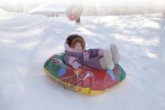 Conducción de la muchacha de una colina de la nieve fotografía de archivo libre de regalías