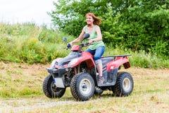 Conducción de la mujer campo a través con la bici del patio Imagen de archivo libre de regalías