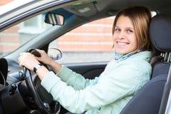 Conducción de la mujer feliz que sostiene la rueda Fotos de archivo