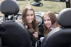 Conducción de las mujeres jovenes Amigos adolescentes que conducen un coche Fotos de archivo libres de regalías