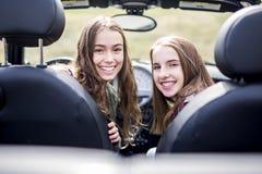 Conducción de las mujeres jovenes Amigos adolescentes que conducen un coche Imagen de archivo libre de regalías