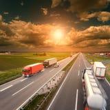 Conducción de los camiones en la falta de definición de movimiento en la carretera en la puesta del sol Imagen de archivo
