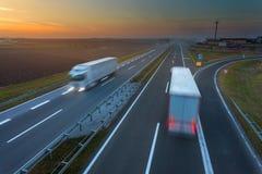 Conducción de los camiones en la falta de definición de movimiento en la carretera en la puesta del sol Fotos de archivo libres de regalías