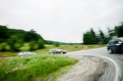 Conducción de tres automóviles en una curva en un camino de la carretera del país Fotografía de archivo