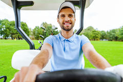 Conducción de un carro de golf Imagen de archivo libre de regalías