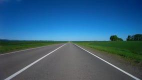 Conducción de un coche en una carretera de asfalto entre los campos agrícolas verdes en un día de verano soleado almacen de video