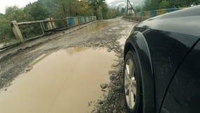 Conducción del camino dañado con los charcos después de lluvia metrajes