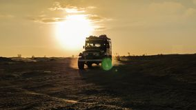 Conducción del coche campo a través en el desierto del Sáhara en la puesta del sol almacen de video