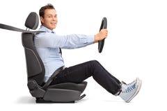 Conducción del hombre joven asentada en el asiento de carro Imágenes de archivo libres de regalías