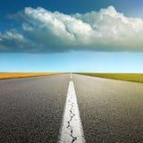 Conducción en la carretera de asfalto a través de los campos Fotografía de archivo libre de regalías