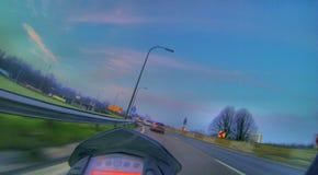 Conducción en la carretera en una motocicleta Foto de archivo