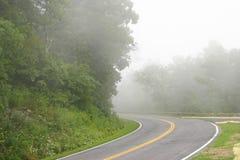 Conducción en un camino brumoso Foto de archivo