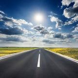 Conducción en una carretera de asfalto vacía hacia el sol fotografía de archivo libre de regalías