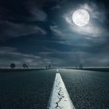 Conducción en una carretera vacía hacia la Luna Llena foto de archivo libre de regalías