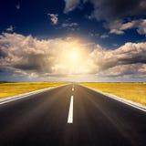 Conducción en una nueva carretera de asfalto vacía en la puesta del sol fotos de archivo libres de regalías