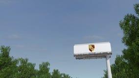 Conducción hacia la cartelera de publicidad con el logotipo de Porsche Representación editorial 3D fotos de archivo libres de regalías