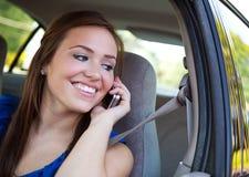 Conducción: Hembra adolescente en el teléfono en coche Imagen de archivo libre de regalías