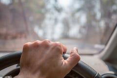 Conducción - la mano del hombre joven que sostiene el volante Fotografía de archivo libre de regalías
