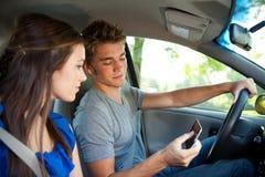 Conducción: Lectura de un mensaje de texto mientras que conduce Foto de archivo
