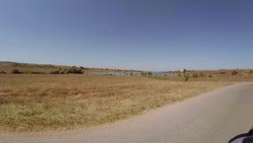 Conducción a lo largo de la carretera nacional de la colina en mediodía soleado Vista del lago y de campos próximos La cámara est almacen de metraje de vídeo