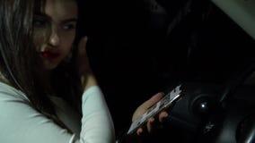 Conducción peligrosa, mujer que enrolla su teléfono mientras que conduce en la noche almacen de metraje de vídeo