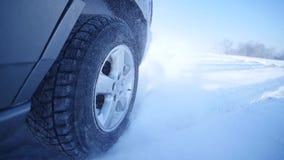 Conducción a través de nieve gruesa con la nieve que chasquea para arriba en cámara almacen de metraje de vídeo