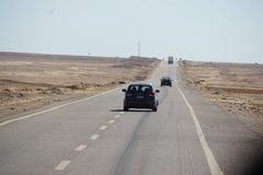 Conducci?n de autom?viles en el camino del desierto foto de archivo libre de regalías