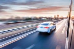 Conducción de automóviles en autopista sin peaje en la puesta del sol, falta de definición de movimiento Imagen de archivo