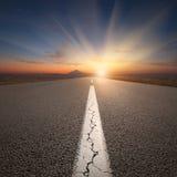 Conducción en el camino abierto hacia la montaña en la salida del sol Foto de archivo libre de regalías