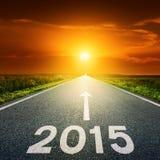Conducción en un camino vacío hacia el sol a 2015 Fotos de archivo
