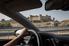 Conducendo un'automobile in strada principale spagnola che passa dal castello dalla città di Maqueda Immagini Stock