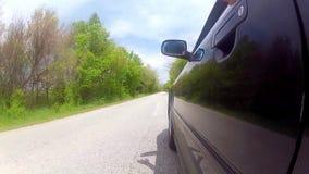 Conduciendo el coche negro con distribuya de ventana almacen de video