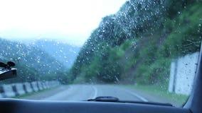 Conduciendo en la lluvia en montañas, camino mojado, POV peligroso almacen de metraje de vídeo