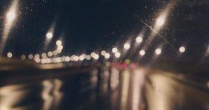 Conduciendo a lo largo de autopista sin peaje en cantidad borrosa noche lluviosa, vista desde adentro del coche almacen de metraje de vídeo