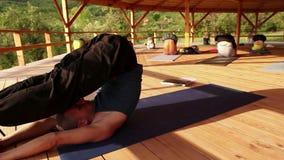 Conductas del instructor de la yoga un asana de ejecución del seminario que arroja sus piernas sobre la cabeza almacen de video