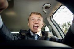 Conducteur agressif derrière la roue d'une voiture Images stock