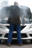 Conducteur automatique et capot ouvert de moteur de voiture dans la fumée du feu Image stock