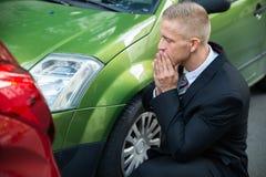 Conducteur bouleversé regardant la voiture après collision du trafic photographie stock libre de droits