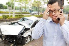 Conducteur bouleversé parlant au téléphone portable avec la voiture d'accident Images stock