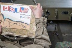 Conducteur d'un regard de véhicule militaire à une carte de la Normandie Image libre de droits