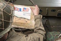 Conducteur d'un regard de véhicule militaire à une carte de la Normandie Images stock